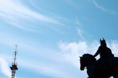 在马背上站立在蓝天和阳光的车手的雕象 库存照片