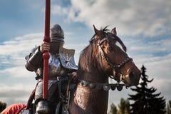 在马背上骑士 在装甲的马有拿着长矛的骑士的 在中世纪战场的马 免版税库存照片