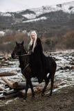 在马背上黑海角的美丽的白肤金发的北欧海盗 库存照片