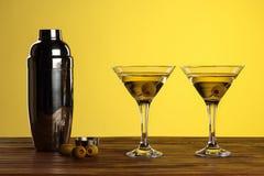 在马蒂尼鸡尾酒玻璃的两个鸡尾酒用绿橄榄和振动器木表面上反对黄色背景与拷贝空间 免版税图库摄影