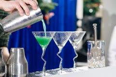 在马蒂尼鸡尾酒玻璃的男服务员倾吐的液体 免版税库存图片