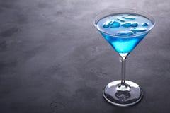 在马蒂尼鸡尾酒玻璃的蓝色冷的鸡尾酒与冰和在玻璃的清楚的露滴在灰色具体背景 库存图片