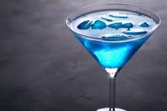在马蒂尼鸡尾酒玻璃的蓝色冷的鸡尾酒与冰和在玻璃的清楚的露滴在灰色具体背景 免版税库存图片