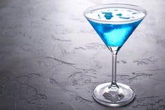 在马蒂尼鸡尾酒玻璃的蓝色冷的鸡尾酒与冰和在玻璃的清楚的露滴在灰色具体背景 图库摄影