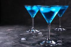 在马蒂尼鸡尾酒玻璃的蓝色冷的鸡尾酒与冰和在玻璃的清楚的露滴在黑暗的背景 免版税图库摄影