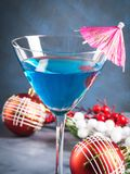 在马蒂尼鸡尾酒玻璃的蓝色鸡尾酒圣诞晚会的 库存照片