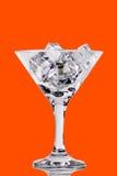 在马蒂尼鸡尾酒玻璃的冰块在颜色背景 免版税库存图片
