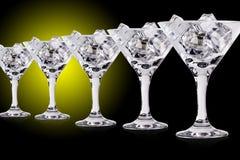 在马蒂尼鸡尾酒玻璃的冰块在颜色背景 库存图片