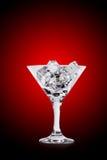 在马蒂尼鸡尾酒玻璃的冰块在颜色背景 图库摄影