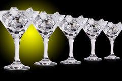 在马蒂尼鸡尾酒玻璃的冰块在颜色背景 免版税库存照片