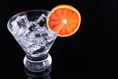 在马蒂尼鸡尾酒玻璃的闪耀的饮料与血橙切片 免版税库存图片