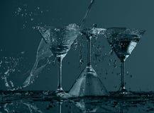 在马蒂尼鸡尾酒玻璃的水飞溅 免版税库存图片