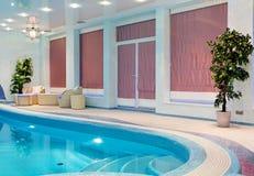 在马赛克游泳池附近的放松区域与家具 免版税图库摄影
