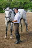 在马附近的骑师立场喂养他 库存图片