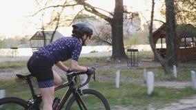 在马鞍外面的被聚焦的适合的女性骑自行车的人骑马 跟随女孩训练侧视图在自行车的 t 影视素材