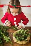 在驯鹿服装佩带的驯鹿鹿角打扮的逗人喜爱的学龄前儿童女孩做圣诞节花圈在客厅 库存照片