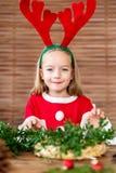 在驯鹿服装佩带的驯鹿鹿角打扮的逗人喜爱的学龄前儿童女孩做圣诞节花圈在客厅 Diy圣诞节 库存照片