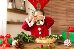 在驯鹿服装佩带的驯鹿鹿角打扮的逗人喜爱的学龄前儿童女孩做圣诞节花圈在客厅 Diy圣诞节 免版税库存照片