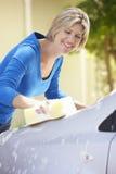 在驱动的妇女洗涤的汽车 免版税库存图片