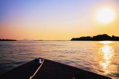 在驾驶在平底锅的小船的日落的惊人的五颜六色的风景 免版税库存照片