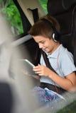 在驾驶在汽车的片剂的小男孩观看的影片 库存照片