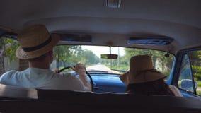 在驾驶在经典葡萄酒汽车的乡下公路的帽子的年轻夫妇 无法认出的对骑马到老汽车里 人和 股票录像