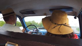 在驾驶在葡萄酒汽车的帽子的年轻夫妇和互相给五 愉快的对骑马到老汽车里 男人和妇女 股票录像