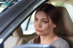 在驾驶有失望,失望鬼脸的轮子后的年轻可爱的白种人妇女一辆汽车或生气 免版税图库摄影