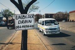 在驾驶的树和的出租汽车的促进标志  库存照片
