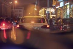 在驾驶穿过城市的出租汽车里面在晚上 免版税库存照片