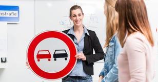 在驾驶课理论上解释交通情况的学习者 图库摄影