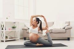 在骆驼姿势的愉快的孕妇训练瑜伽 免版税图库摄影