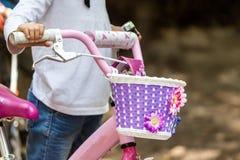 在骑她的自行车的逗人喜爱的女孩的看法 免版税图库摄影