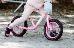 在骑她的自行车的逗人喜爱的女孩的看法 图库摄影