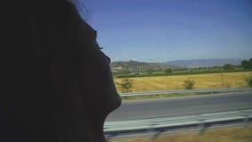 在骑马期间女孩的剪影在公共汽车上,睡觉在窗口 影视素材