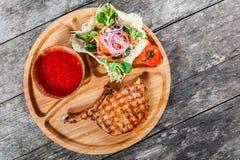 在骨头、新鲜的沙拉、烤菜和西红柿酱的烤牛排在木背景的切板 库存图片
