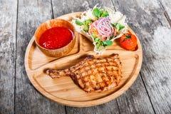 在骨头、新鲜的沙拉、烤菜和西红柿酱的烤牛排在木背景的切板 免版税库存照片