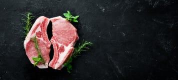 在骨头的未加工的牛排 肉用香料和草本 在黑石背景 免版税库存图片