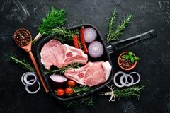 在骨头的未加工的牛排 肉用香料和草本 在黑石背景 免版税库存照片