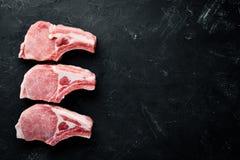 在骨头的未加工的牛排 肉用香料和草本 在黑石背景 免版税图库摄影