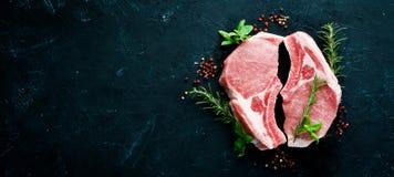 在骨头的未加工的牛排 肉用香料和草本 在黑石背景 图库摄影