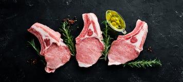 在骨头的未加工的牛排 肉香料和草本与 在黑石背景 库存图片