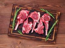 在骨头的未加工的羊羔炸肉排在黑褐色木背景,羊羔肋骨,顶视图 库存图片