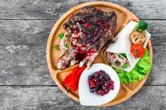在骨头的烤Ribeye牛排用莓果调味汁、新鲜的沙拉和烤菜在切板在木背景 免版税图库摄影