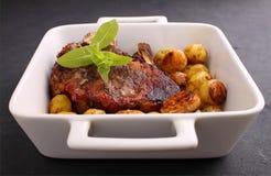 在骨头的牛排在与菜的白色盘烘烤了 免版税库存照片