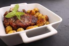 在骨头的牛排在与菜的白色盘烘烤了 库存图片