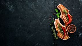 在骨头的牛排用迷迭香 格栅,烤肉 在黑石背景 库存照片