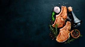 在骨头的牛排用迷迭香 格栅,烤肉 在黑石背景 免版税图库摄影