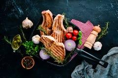 在骨头的牛排用迷迭香 格栅,烤肉 在黑石背景 免版税库存照片