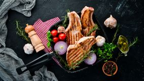 在骨头的牛排用迷迭香 格栅,烤肉 在黑石背景 库存图片